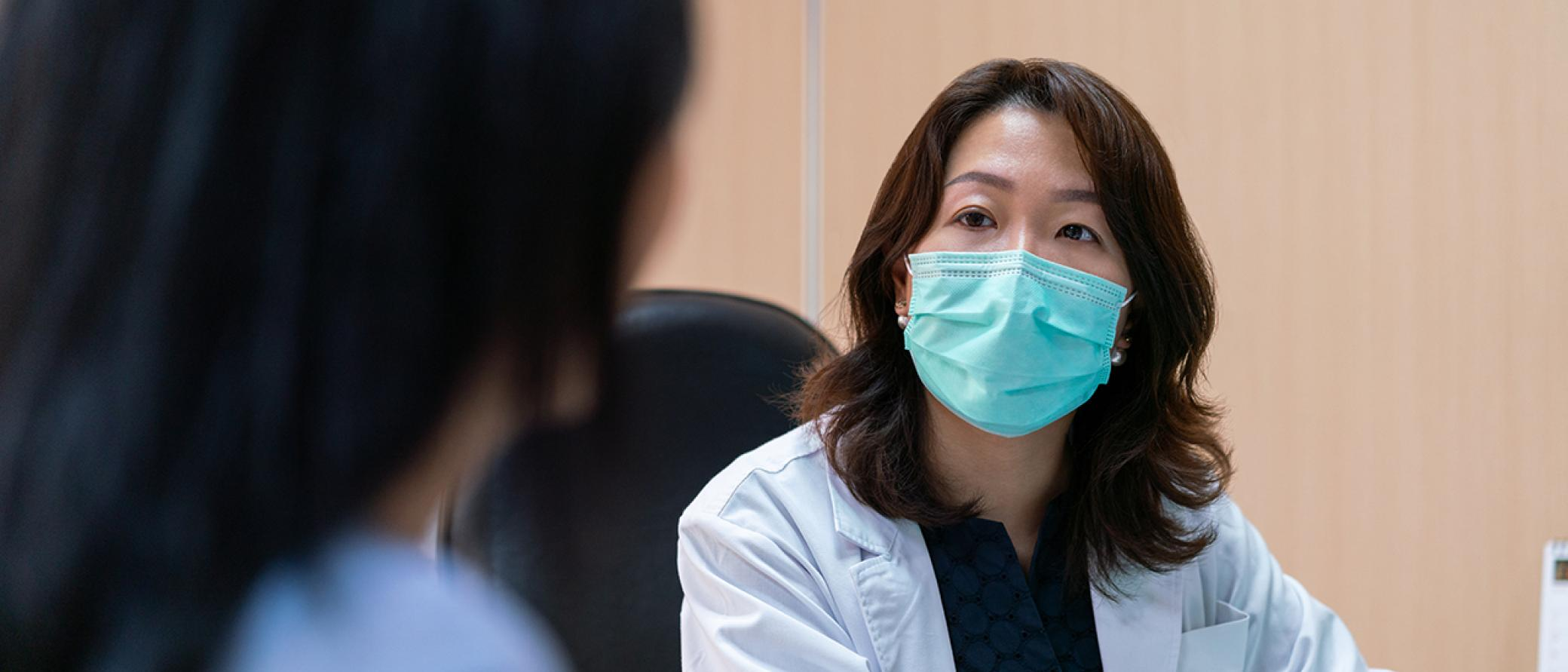 Doctor with mask looking at patient in clinic